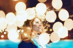 Mujer sorprendente por las luces de hadas en la Navidad foto de archivo