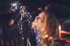 Mujer sorprendente por las luces de hadas en la noche imagen de archivo libre de regalías