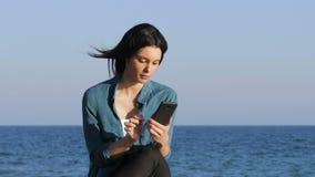 Mujer sorprendente que encuentra ofertas en el teléfono en la playa metrajes