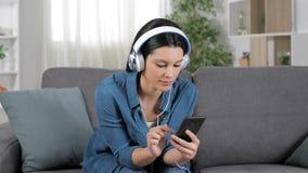 Mujer sorprendente que escucha la música en un sofá metrajes