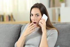 Mujer sorprendente que habla en el teléfono que le mira Imagen de archivo