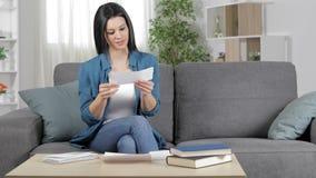 Mujer sorprendente que lee un recibo en casa almacen de video