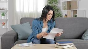 Mujer sorprendente que lee una letra en casa almacen de video