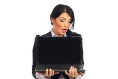 Mujer sorprendente que mira para esconder la pantalla de la computadora portátil Fotografía de archivo