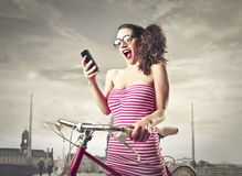Mujer sorprendente que mira su teléfono móvil Foto de archivo