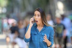 Mujer sorprendente que recibe noticias en el teléfono Imagen de archivo libre de regalías