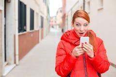 Mujer sorprendente que recibe noticias impactantes en un teléfono elegante en el str imagenes de archivo