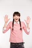 Mujer sorprendente que se coloca con las manos aumentadas para arriba Imagen de archivo
