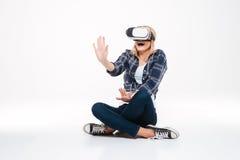 Mujer sorprendente que se sienta en el piso que lleva los vidrios de VR Imagen de archivo libre de regalías