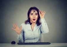 Mujer sorprendente que trabaja en el ordenador con el teclado que mira en sorpresa la pantalla imagen de archivo libre de regalías