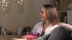 Mujer sorprendente que ve la TV en la noche en casa almacen de video
