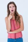 Mujer sorprendida con el finger en la barbilla Foto de archivo libre de regalías