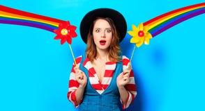 Mujer sorprendida con el molinillo de viento y el arco iris Fotos de archivo