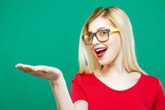 Mujer sorprendida con el pelo rubio largo, las lentes y el top rojo llevando a cabo el espacio vacío en su mano en fondo verde ad Foto de archivo