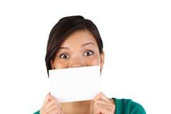 Mujer sorprendida con la tarjeta en blanco Imagen de archivo