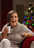 Mujer sorprendida con la taza de bebida que mira la TV Foto de archivo libre de regalías