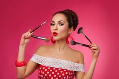 Mujer sorprendida con los cepillos del maquillaje Ella es imagenes de archivo