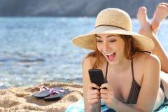 Mujer sorprendida divertida que mira medios sociales en un teléfono elegante en la playa Imagen de archivo