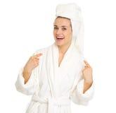 Mujer sorprendida en albornoz que señala en sí misma Fotografía de archivo libre de regalías
