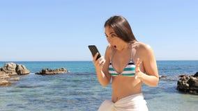 Mujer sorprendida en contenido del teléfono de la lectura del bikini en la playa metrajes