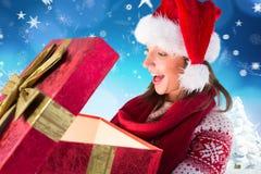 Mujer sorprendida en el sombrero de santa que mira los regalos de la Navidad Fotografía de archivo