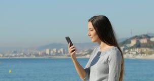 Mujer sorprendida en el teléfono en la playa almacen de video