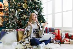 Mujer sorprendida en línea en el ordenador portátil en el interior de la Navidad Fotos de archivo