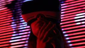 Mujer sorprendida en las auriculares de la realidad virtual, nueva experiencia, progreso de la tecnología metrajes