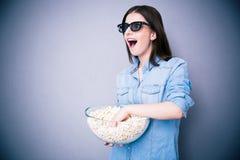Mujer sorprendida en los vidrios del cine que sostienen el cuenco con palomitas Imágenes de archivo libres de regalías