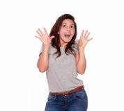 Mujer sorprendida en vaqueros que grita con las manos para arriba Imagen de archivo