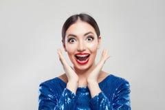 Mujer sorprendida feliz en apoyos en los dientes en el fondo blanco Muchacha emocionada con los apoyos que se divierten imagen de archivo