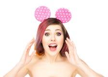 Mujer sorprendida hermosa en los oídos de Mickey Mouse Imagenes de archivo