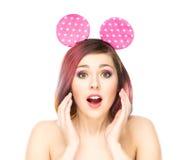 Mujer sorprendida hermosa en los oídos de Mickey Mouse Fotografía de archivo