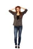 Mujer sorprendida jóvenes que lleva a cabo las manos dentro del pelo Imagen de archivo libre de regalías