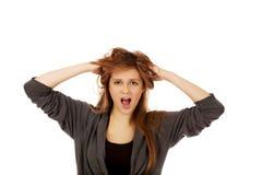 Mujer sorprendida jóvenes que lleva a cabo las manos dentro del pelo Imagen de archivo