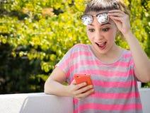 Mujer sorprendida moderna joven que usa su teléfono móvil Foto de archivo