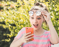 Mujer sorprendida moderna joven que usa su teléfono móvil Imagenes de archivo