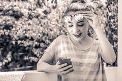 Mujer sorprendida moderna joven que usa su teléfono móvil Imagen de archivo libre de regalías