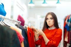 Mujer sorprendida que comprueba el precio en un vestido en la estación de la venta Foto de archivo libre de regalías