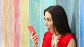 Mujer sorprendida que comprueba el teléfono en una pared colorida metrajes