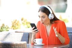 Mujer sorprendida que encuentra ofertas de la m?sica en el tel?fono foto de archivo