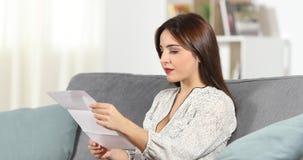Mujer sorprendida que lee una letra en casa metrajes