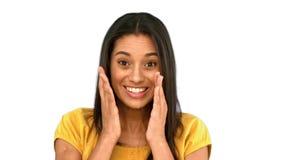 Mujer sorprendida que lleva a cabo su cabeza en el fondo blanco metrajes