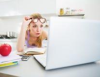Mujer sorprendida que mira en ordenador portátil mientras que estudia en cocina Imagen de archivo