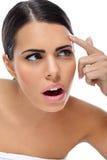 Mujer sorprendida que mira problema en su piel Fotos de archivo