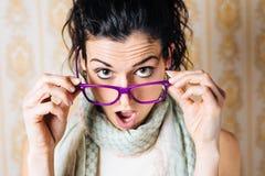 Mujer sorprendida que mira sobre los vidrios Imagenes de archivo