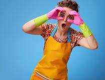 Mujer sorprendida que mira a través de las manos formadas binoculares en azul Foto de archivo
