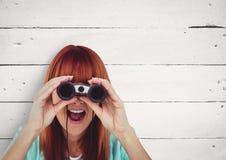 Mujer sorprendida que mira a través de los prismáticos contra el fondo blanco Fotos de archivo libres de regalías