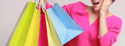 Mujer sorprendida que presenta con los bolsos de compras y que mira la cámara foto de archivo libre de regalías
