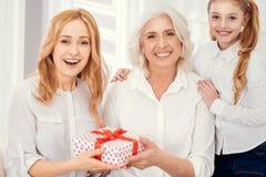 Mujer sorprendida que recibe el regalo de su mamá e hija Imagen de archivo